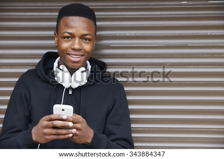 Teenage Boy Listening To Music And Using Phone In Urban Setting - stock photo