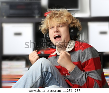 Teenage boy listening to the music and singing - stock photo