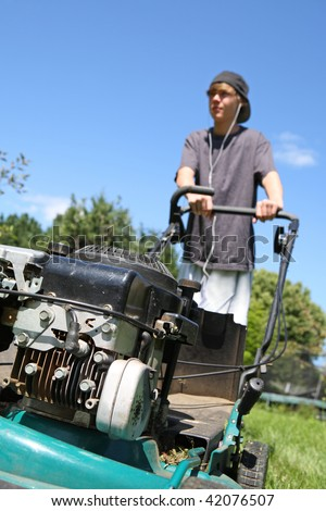 Teenage boy mowing the lawn wearing headphones - stock photo