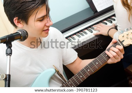 Teenage boy playing electric guitar and singing while girl plays on piano. - stock photo