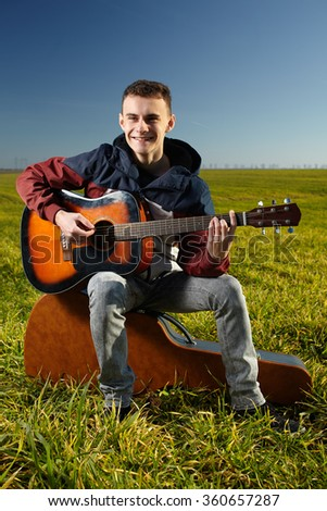 Teenage boy playing guitar outdoor in a grass field - stock photo