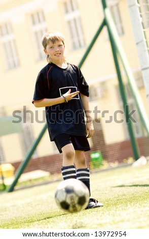 Teenage boy playing soccer at sunny day - stock photo