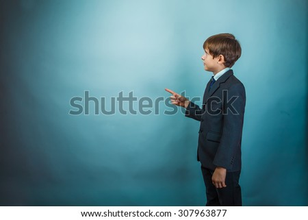 Teenage boy pointing at a businessman standing with his back background photo studio - stock photo