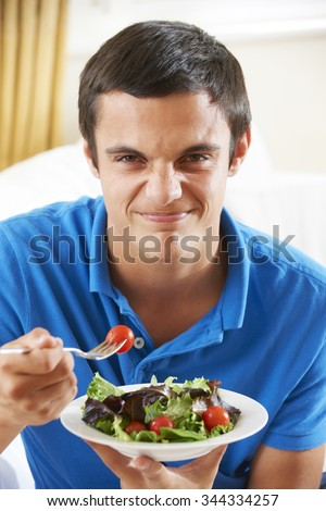 Teenage Boy Pulling Face Whilst Eating Healthy Salad - stock photo