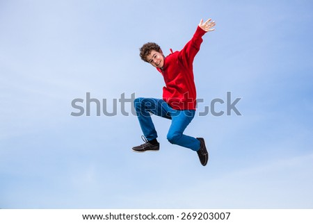 Teenage boy running, jumping outdoor - stock photo