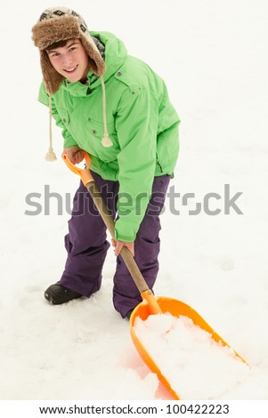 Teenage Boy Shovelling Snow From Path - stock photo