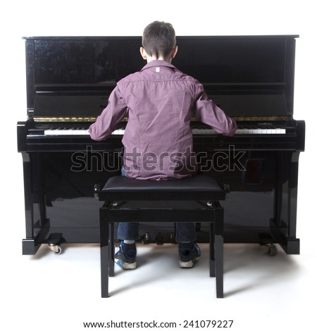 teenage boy sits at upright piano in studio with white background - stock photo