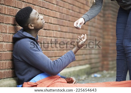 Teenage Boy Sleeping On The Street Being Given Money - stock photo
