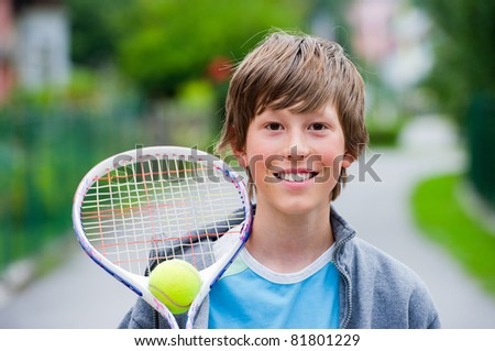 Teenage boy smiling while holding a tennis racket and ball. - stock photo