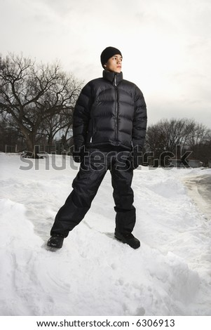 Teenage boy standing in snow wearing winter clothes. - stock photo
