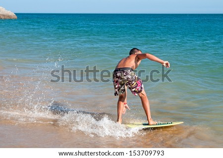 teenage boy surfing in the beach - stock photo