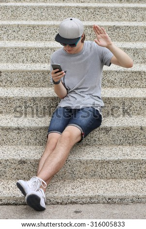 Teenage boy typing text message.Using smart phone - stock photo