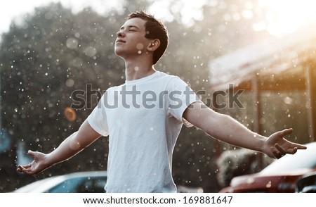 teenage boy under rain in the city - stock photo