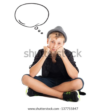 Teenage boy wearing casual clothes and hat sitting on the floor with a thoughtful face. Nearby speech bubble. - stock photo