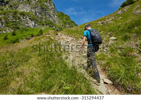 Teenage boy with backpack hiking into the rocky mountains - stock photo