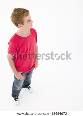 Teenage boy with hands in pockets - stock photo