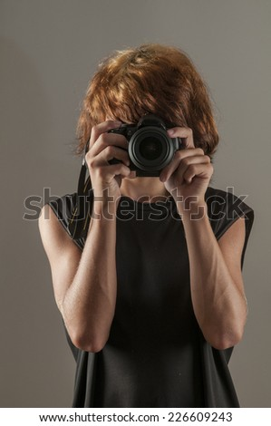Teenage boy with punk dyed hair taking photograph - stock photo