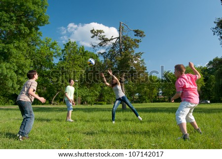 Teenage boys and girls playing with the ball in the park on sunny spring day. - stock photo