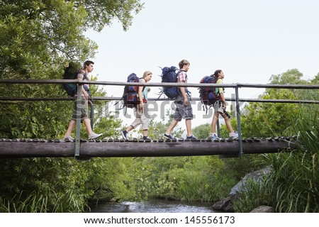 Teenage boys and girls with backpacks walking on bridge in forest - stock photo