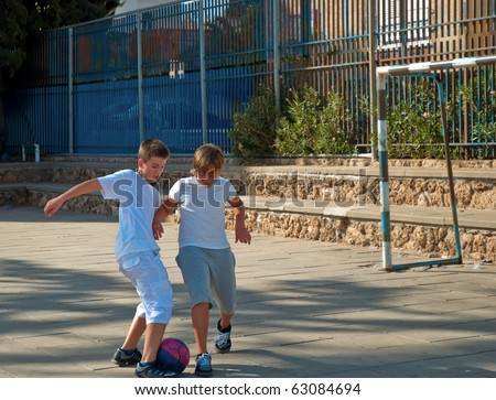 Teenage boys playing soccer at sunny day . - stock photo