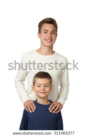 Teenage boys stands behind putting hands on his little brother shoulders isolated on white background - focus on little boy face - stock photo