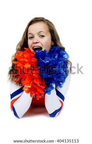 Teenage cheerleader laying down with pom poms - stock photo