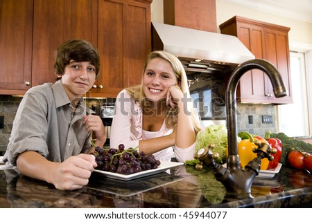 Teenage children in kitchen with fruits and vegetables on counter - stock photo