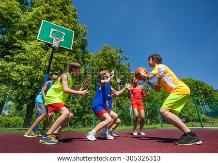 Teenage children playing basketball game together - stock photo