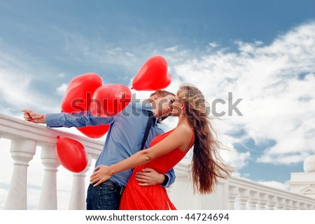 Teenage couple embracing over sky and holding bunch of baloons-hearts - stock photo