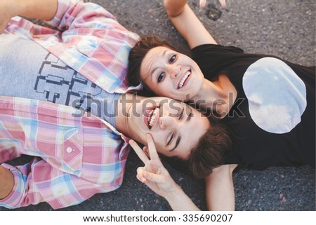 Teenage couple lying down and laughing. Loving girl and young man lying head to head. Top view. - stock photo