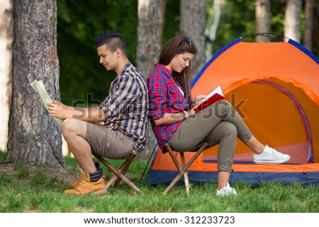 Teenage couple sitting back to back in front of the tent, young man looking at maps while girl is reading a book - stock photo