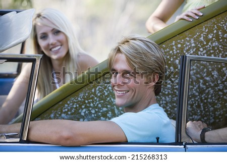 Teenage couple sitting in car with surfboard, smiling, side view, portrait - stock photo