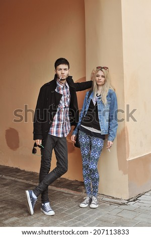 Teenage couple smoking - stock photo