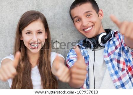 Teenage couple with thumbs up - stock photo
