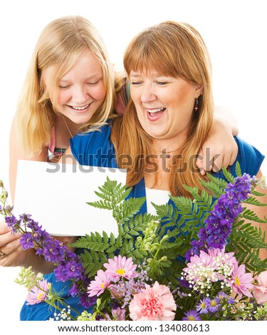 Teenage daughter giving flowers and a card to her mother on Mother's Day.  Card blank ready for your text. - stock photo