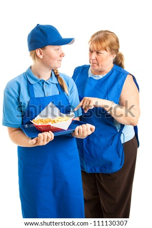 Teenage fast food worker getting instructions from her middle-aged boss.  Isolated on white. - stock photo