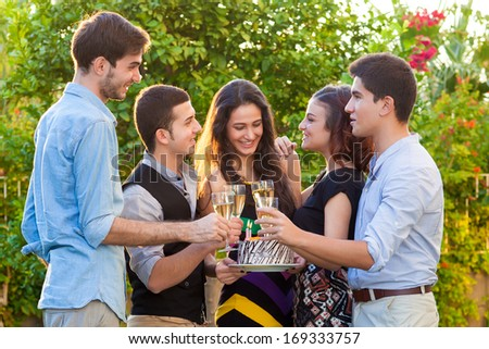 Teenage friends celebrating at a birthday party drinking champagne in elegant flutes and congratulating a beautiful happy, girl holding a birthday cake with burning candles - stock photo