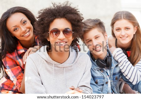 Teenage friends. Four cheerful teenage friends sitting close to each other and smiling at camera - stock photo