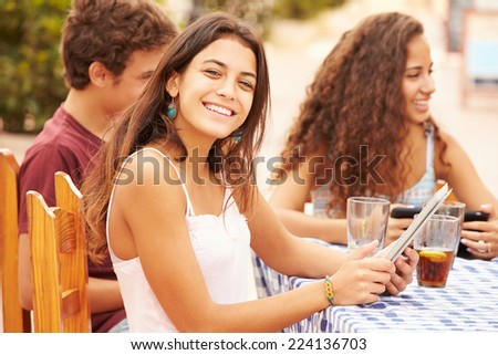 Teenage Friends Sitting At Caf�¢?? Using Digital Devices - stock photo