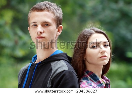teenage girl and boy portrait standing outdoor in green park - stock photo