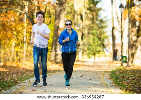 Teenage girl and boy running in city park  - stock photo