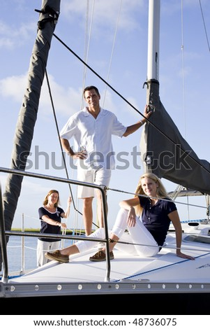 Teenage girl and parents relaxing on sailboat at dock on sunny day - stock photo
