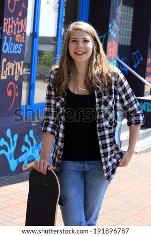 Teenage girl and skateboard in front of a colorful music related background. - stock photo