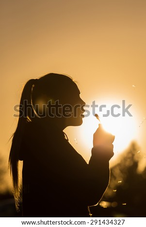 teenage girl backlit by the sun blowing a dandelion seed head, seeds catching the sunlight Copy space to the right top of image - stock photo