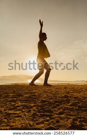 teenage girl  balancing on slackline  on the beach in sunrise silhoutte - stock photo