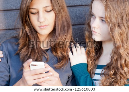 Teenage girl comforting her friend reading sad message - stock photo