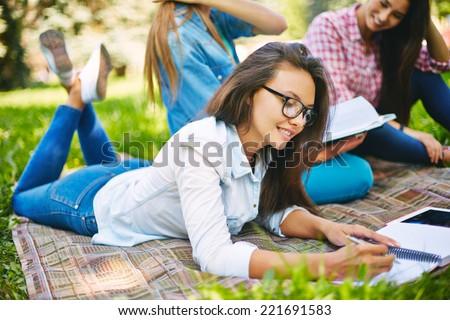 Teenage girl doing her homework in park - stock photo