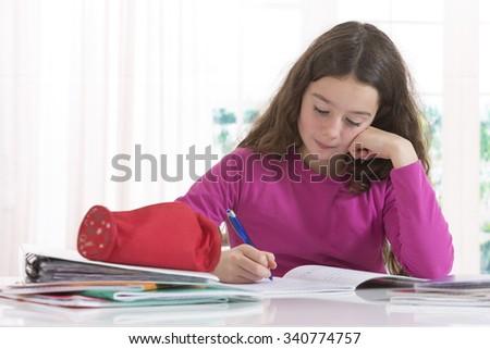 Teenage girl doing homework for school.  - stock photo