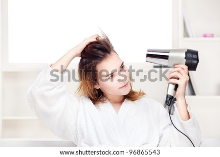 Teenage girl drying her hair at home - stock photo