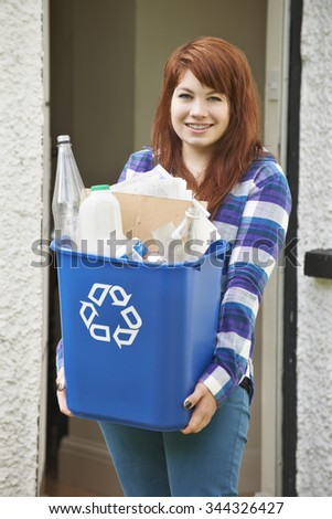 Teenage Girl Emptying Recycling At Home - stock photo